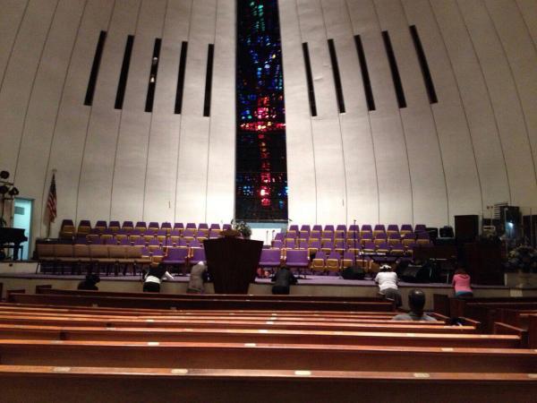 Gente rezando y entrando en Trance. El párroco está debajo del altar tumbado, en una Misa Gospel en Harlem